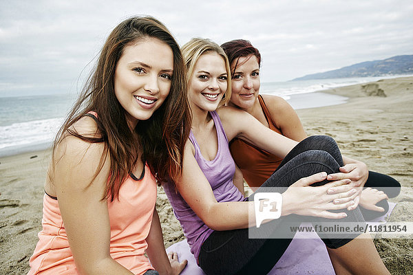 Portrait of smiling Caucasian women sitting on beach