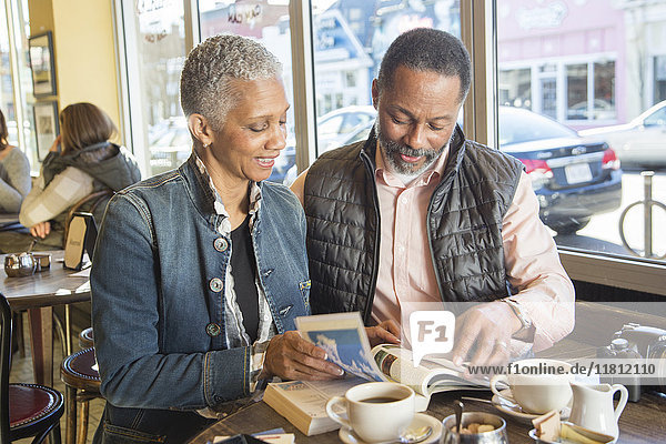 Mixed Race couple reading travel guidebook in coffee shop