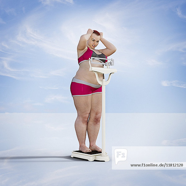 Frustrated woman checking weight on scale
