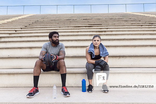 Trainer and woman resting on bleachers
