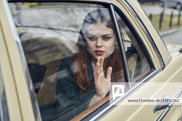 Pensive Caucasian woman in back seat of car leaning on window