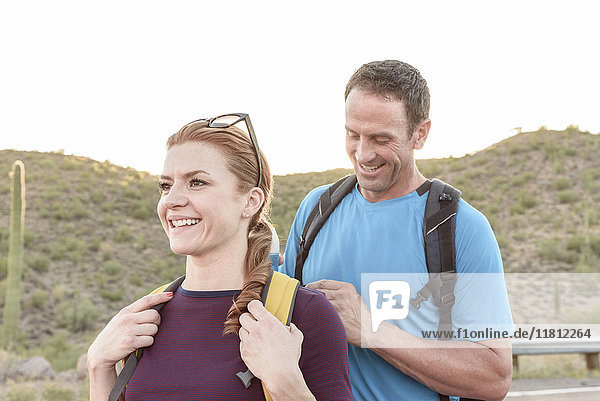 Man helping woman with backpack