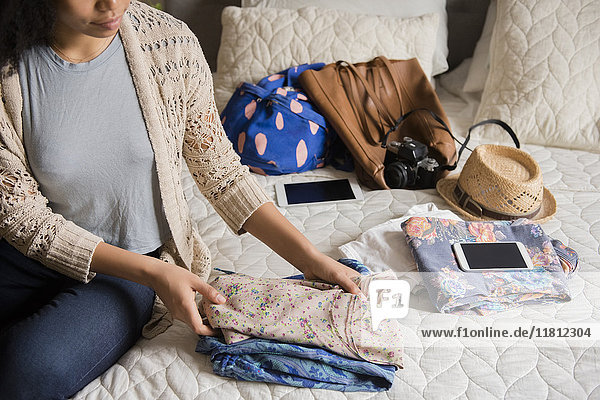 African American woman sitting on bed folding clothing