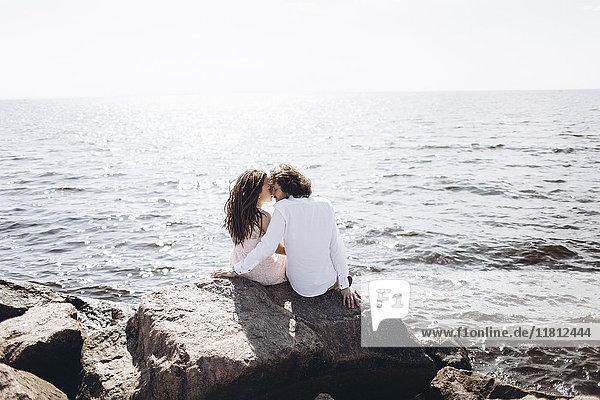 Middle Eastern couple sitting on rocks near ocean