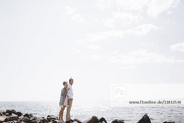 Paar aus dem Nahen Osten steht auf Felsen am Meer