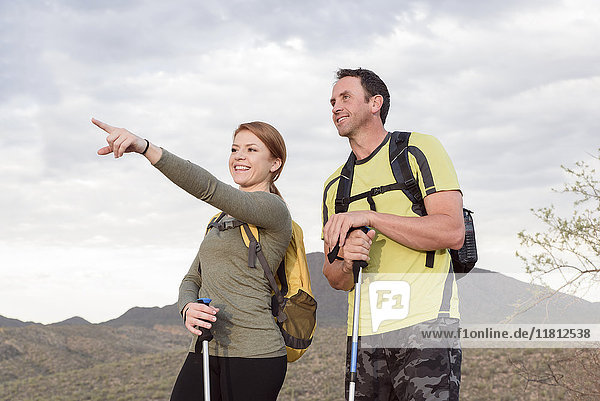 Woman pointing to man in desert while hiking