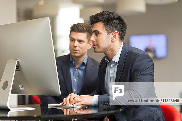 Two businessmen looking at office desktop computer