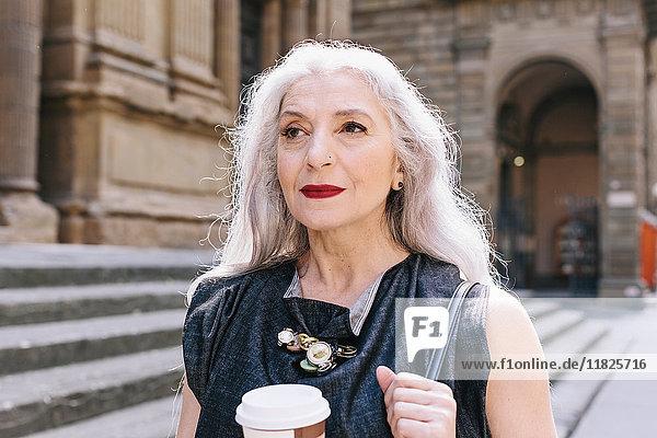 Reife Frau mit langen grauen Haaren mit Kaffee auf der Straße in Florenz  Italien