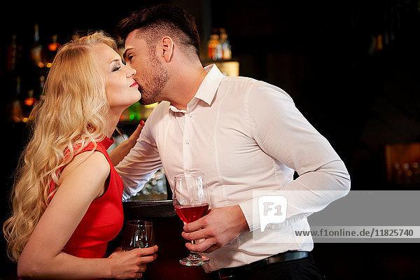 Glamouröses Paar küsst sich an der Bar auf die Wange