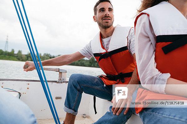 Man and woman on sailing boat  man steering boat