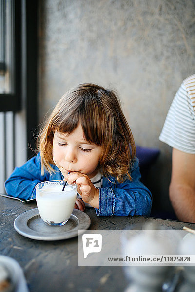Girl sipping milk in cafe