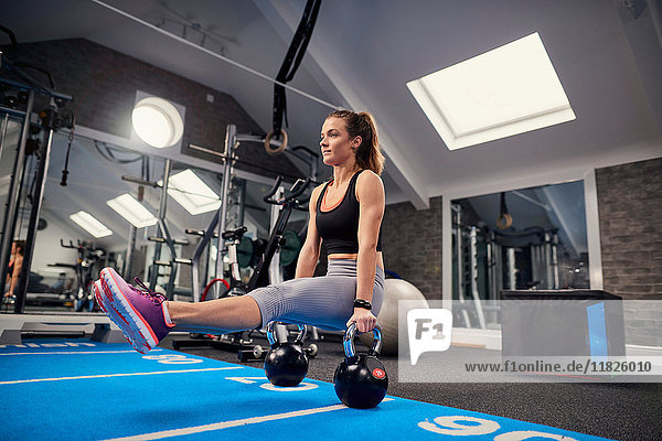 Young woman training  doing sit up push ups on kettle bells in gym
