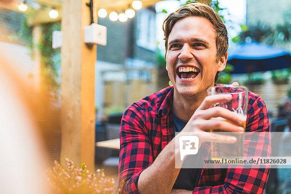 Paar sitzt im Gastgarten  hält einen Krug Bier in der Hand und lacht