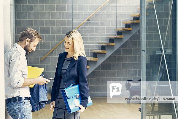 Geschäftsmann und -frau schauen auf Smartphone im Großraumbüro