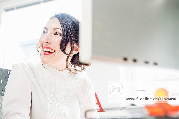 Weibliche Büroangestellte schaut weg  lächelt