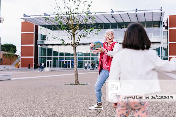 Reife Frau und Mädchen spielen mit fliegender Scheibe in der Stadt
