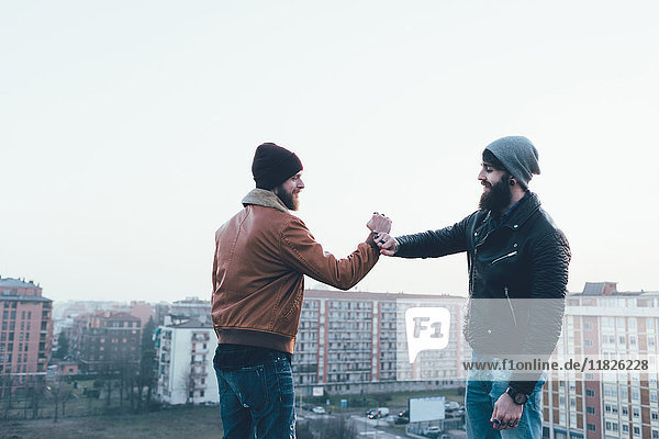 Two young male hipsters fist bumping above cityscape
