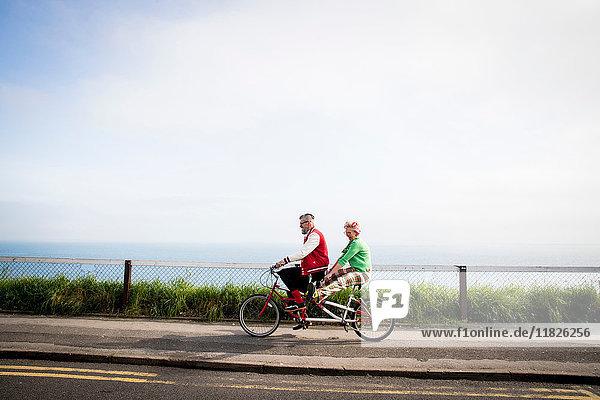 Schrulliges Paar beim Sightseeing auf dem Tandemfahrrad  Bournemouth  England