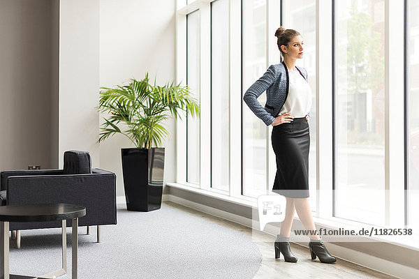 Young confident businesswoman looking through office window
