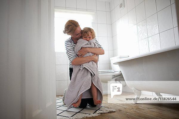 Mutter und Tochter im Badezimmer  Mutter wickelt die Tochter in ein Badetuch und umarmt sie