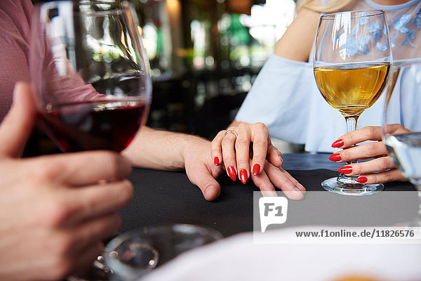 Geschnittene Ansicht der Hand der Frau auf der Hand des Freundes am Restauranttisch
