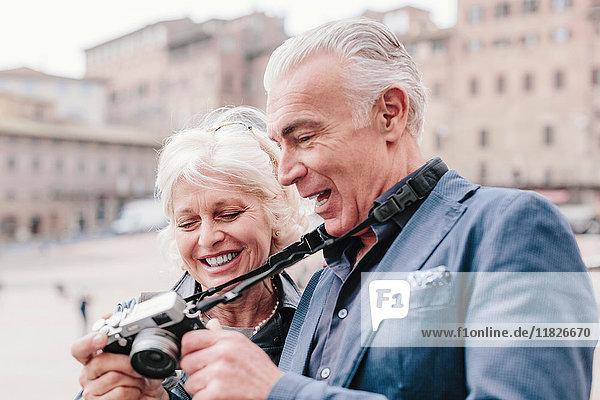 Touristenpaar bespricht Digitalkamera auf dem Stadtplatz  Siena  Toskana  Italien