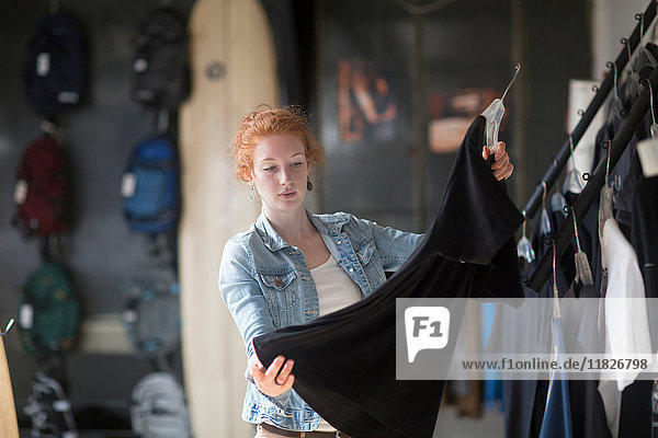 Woman working in board shop  organising clothes on rail