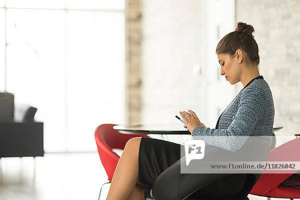 Geschäftsfrau sitzt im Büro und schaut auf ihr Smartphone