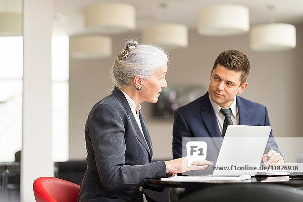 Geschäftsfrau erklärt einem männlichen Kollegen in einer Vorstandssitzung