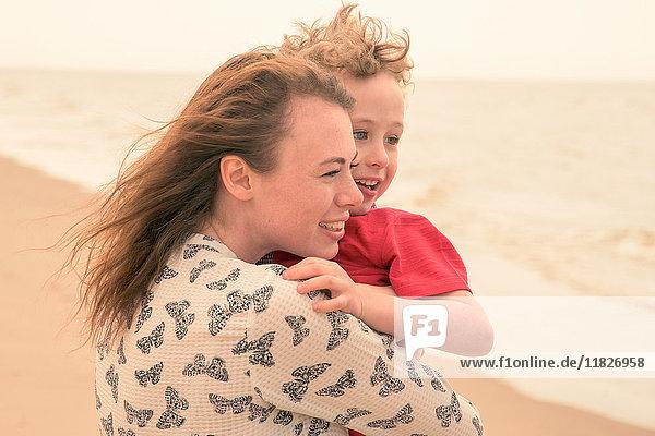 Junge Frau trägt Sohn am Strand