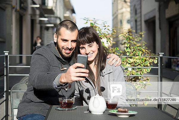Junges Paar sitzt vor einem Café  macht sich selbstständig  benutzt ein Smartphone