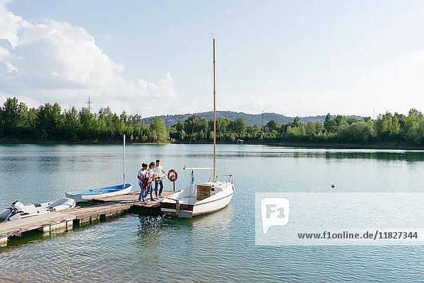 Friends standing on pier  boarding sailing boat
