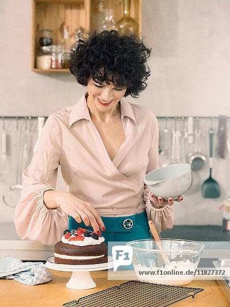 Frau dekoriert Schokoladenkuchen mit Milchcreme und frischen Sommerfrüchten