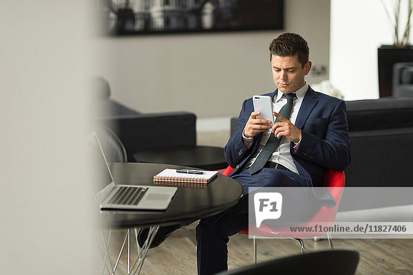 Businessman sitting in office looking at smartphone