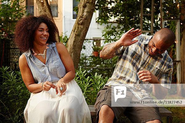 Mittelgroßer erwachsener Mann lacht mit Frau auf Gartenparty