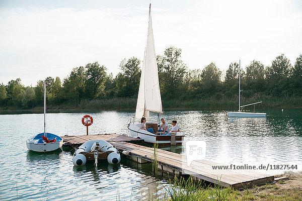 Drei Freunde entspannen sich auf einem Segelboot auf dem See