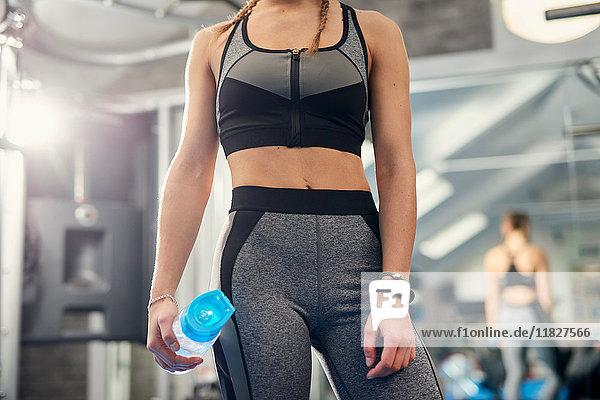 Mittlerer Abschnitt des Trainings einer jungen Frau mit einer Wasserflasche in der Turnhalle