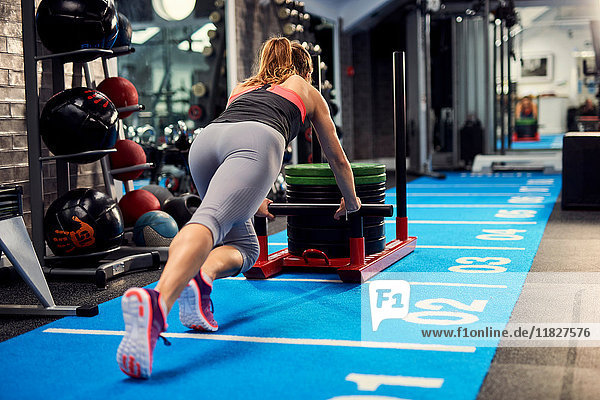 Rear view of young woman training  pushing weight sled in gym