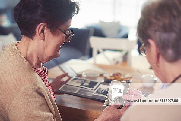 Über-Schulter-Ansicht von zwei älteren Frauen  die sich alte Fotos bei Tisch anschauen