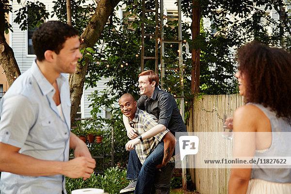 Junges Paar beobachtet Freunde beim Gartenfest huckepack