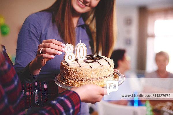 Tochter bereitet Geburtstagskuchen für Mutter auf Geburtstagsfeier