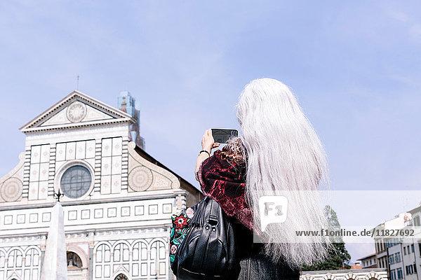 Langhaarige grauhaarige Frau fotografiert die Kirche Santa Maria Novella  Florenz  Italien