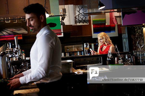 Verärgerte junge Frau schaut auf Smartphone  während sie an der Bar sitzt
