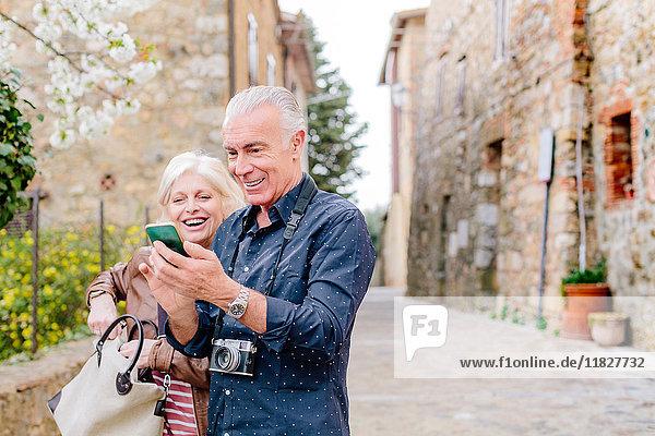 Touristenpaar betrachtet Smartphone auf gepflasterter Straße  Siena  Toskana  Italien