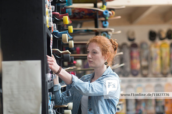 Woman working in skateboard shop  putting skateboard on shelf