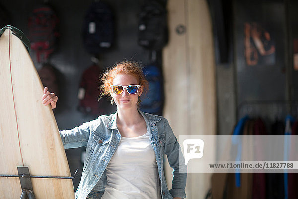 Woman working in board shop  holding surfboard