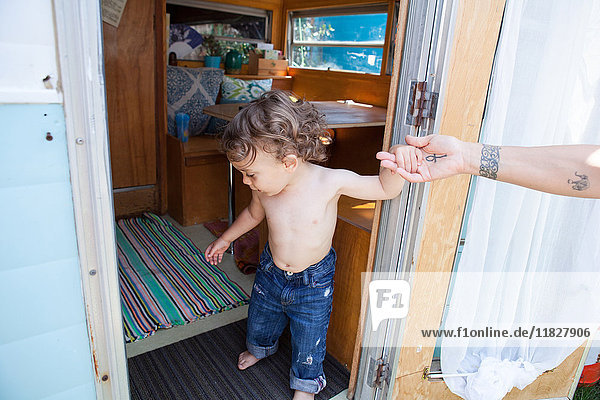 Father helping son in doorway of trailer home