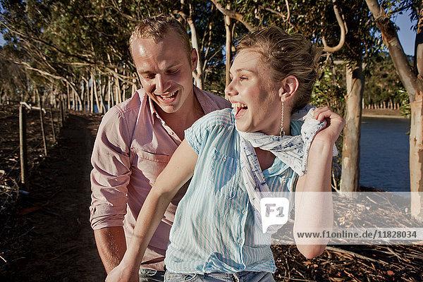 Junges lachendes Paar im Wald