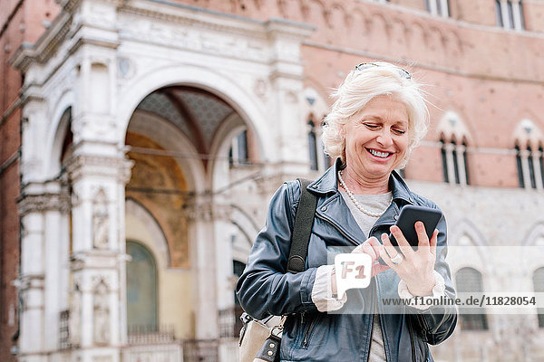 Mature woman looking at smartphone in city  Siena  Tuscany  Italy