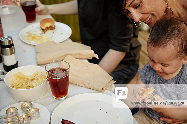 Mother holding baby boy at table at garden party  smiling